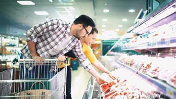 Man Selecting Meat from Grocer