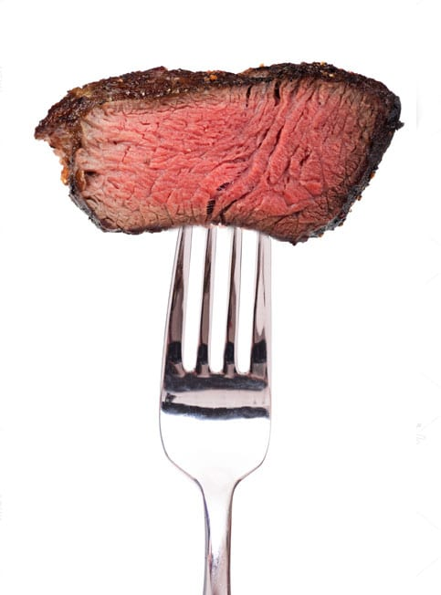 Fork holding perfectly cooked steak