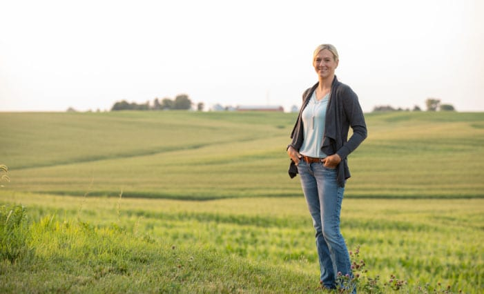 Female farmer in front of an open field